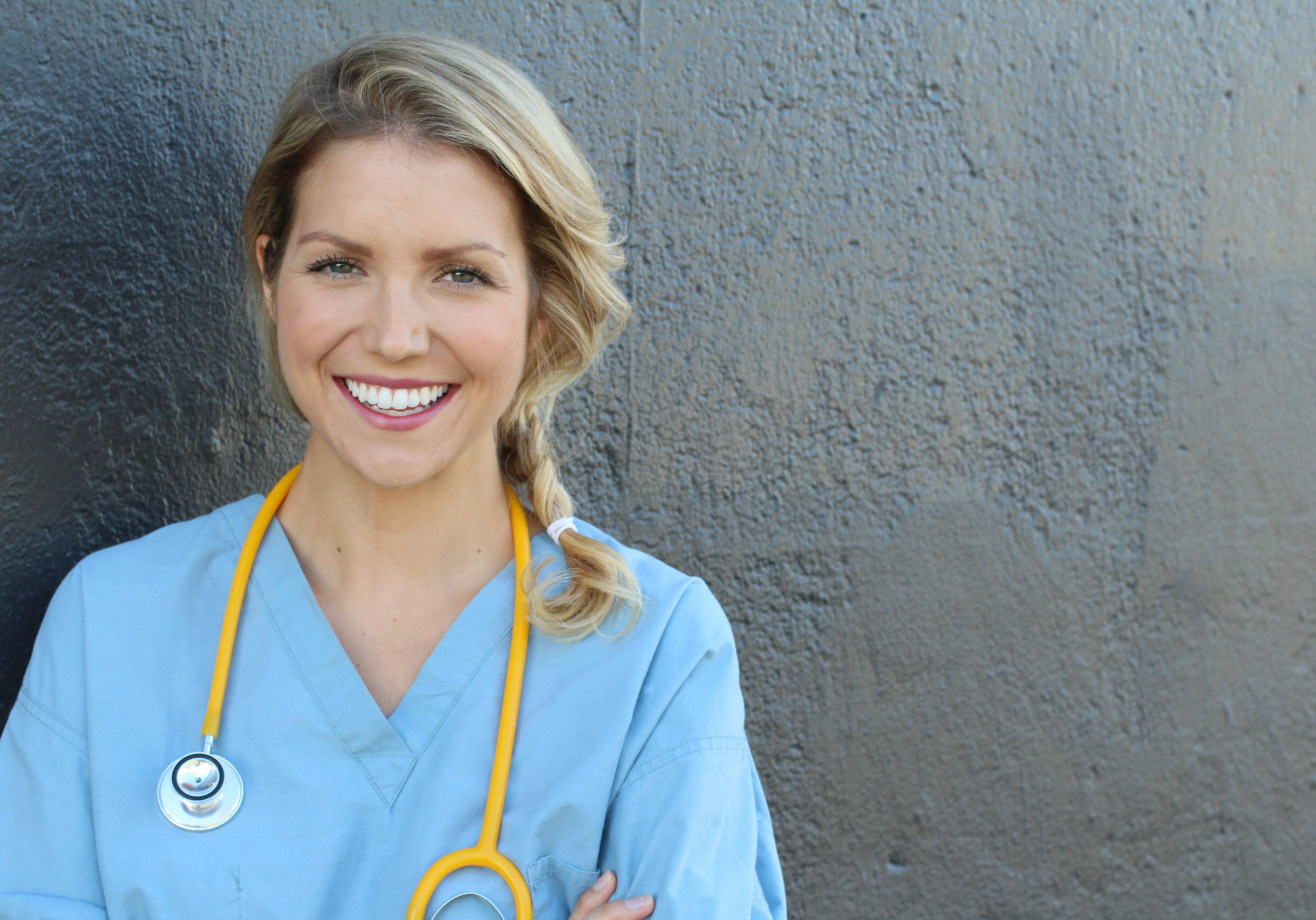 Nurse with long blonde hair and a stethoscope in a uniform smiling at the camera.