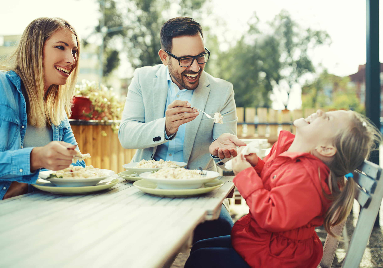 Happy family is enjoying pasta in restaurant.