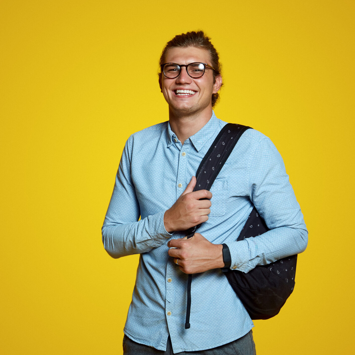 Handsome young student in blue casual shirt and eyeglasses holding backpack and smiling at camera on yellow background. Handsome man laughing and standing isolated over yellow wall.
