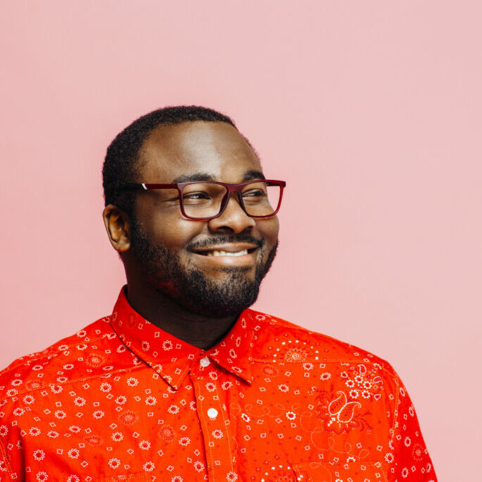 Man in bright red shirt and glasses  smiling and looking off camera against pink background