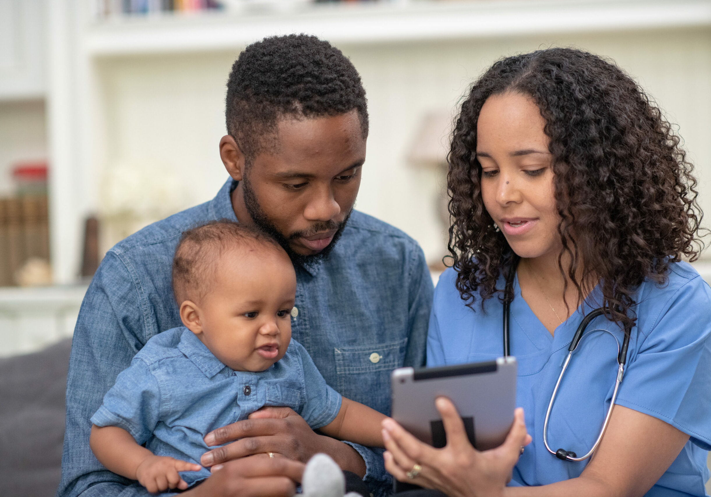 A female doctor of African descent is checking on a patient at their home. They are meeting in the family's living room. The patient is a toddler girl. The child is sitting on her father's lap. The doctor is holding a tablet computer.