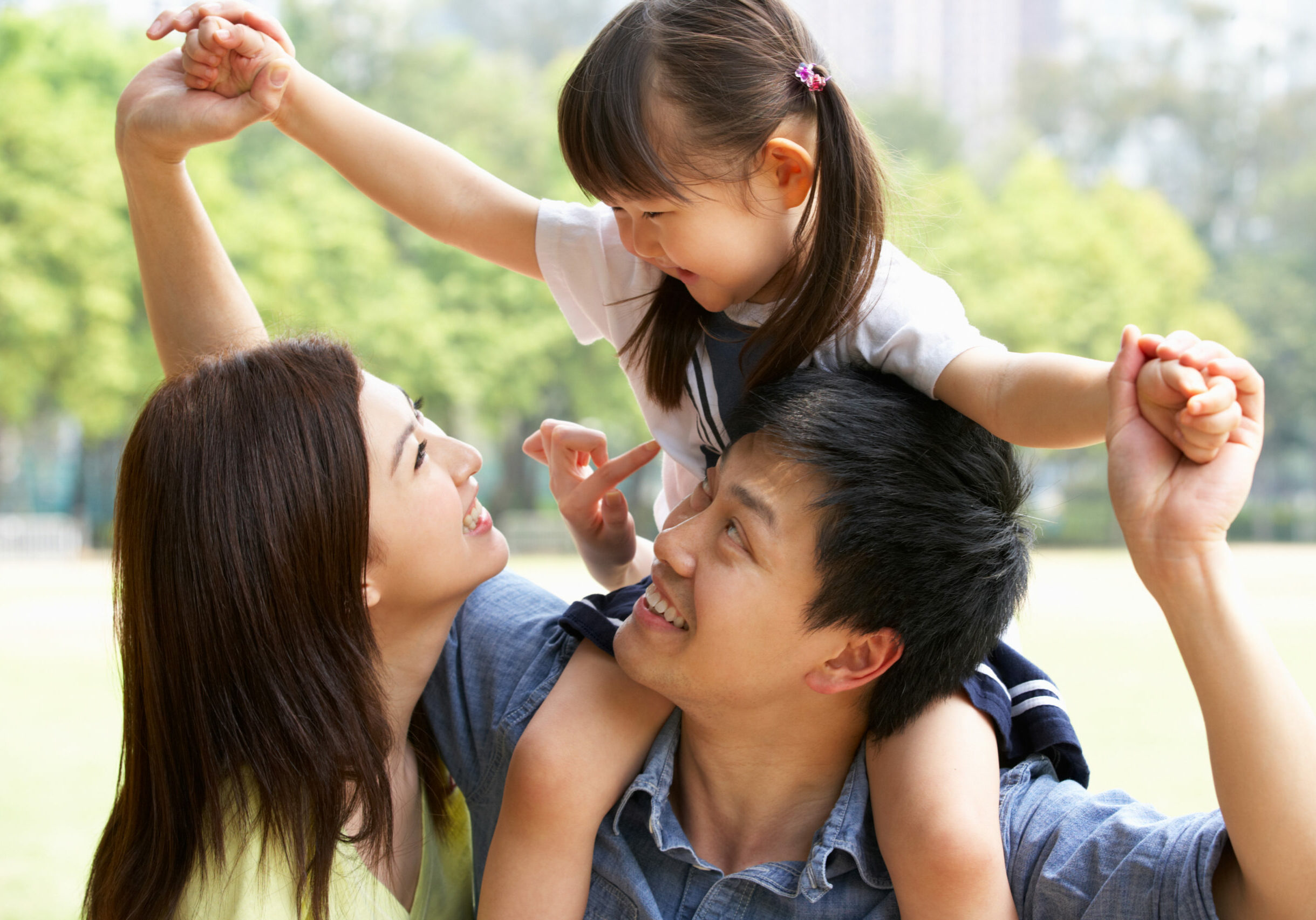 Chinese Family Giving Daughter Ride On Shoulders In Park Looking At Each Other Having Fun Smiling
