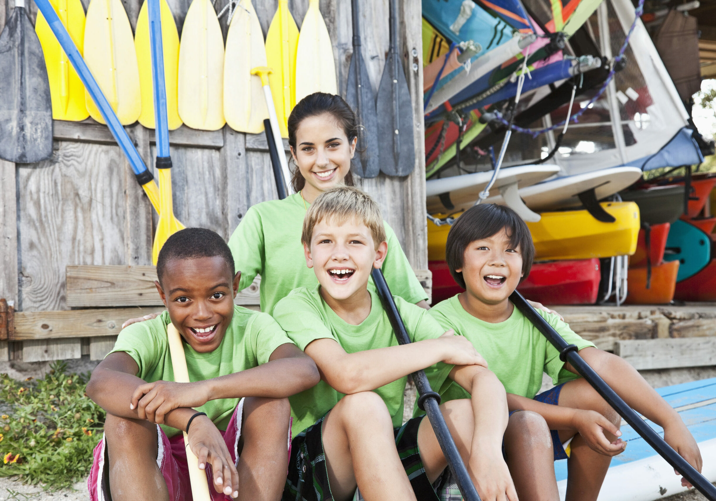 Teenage girl (17 years) with boys (8-9 years) sitting on paddle board at water sports equipment shack.