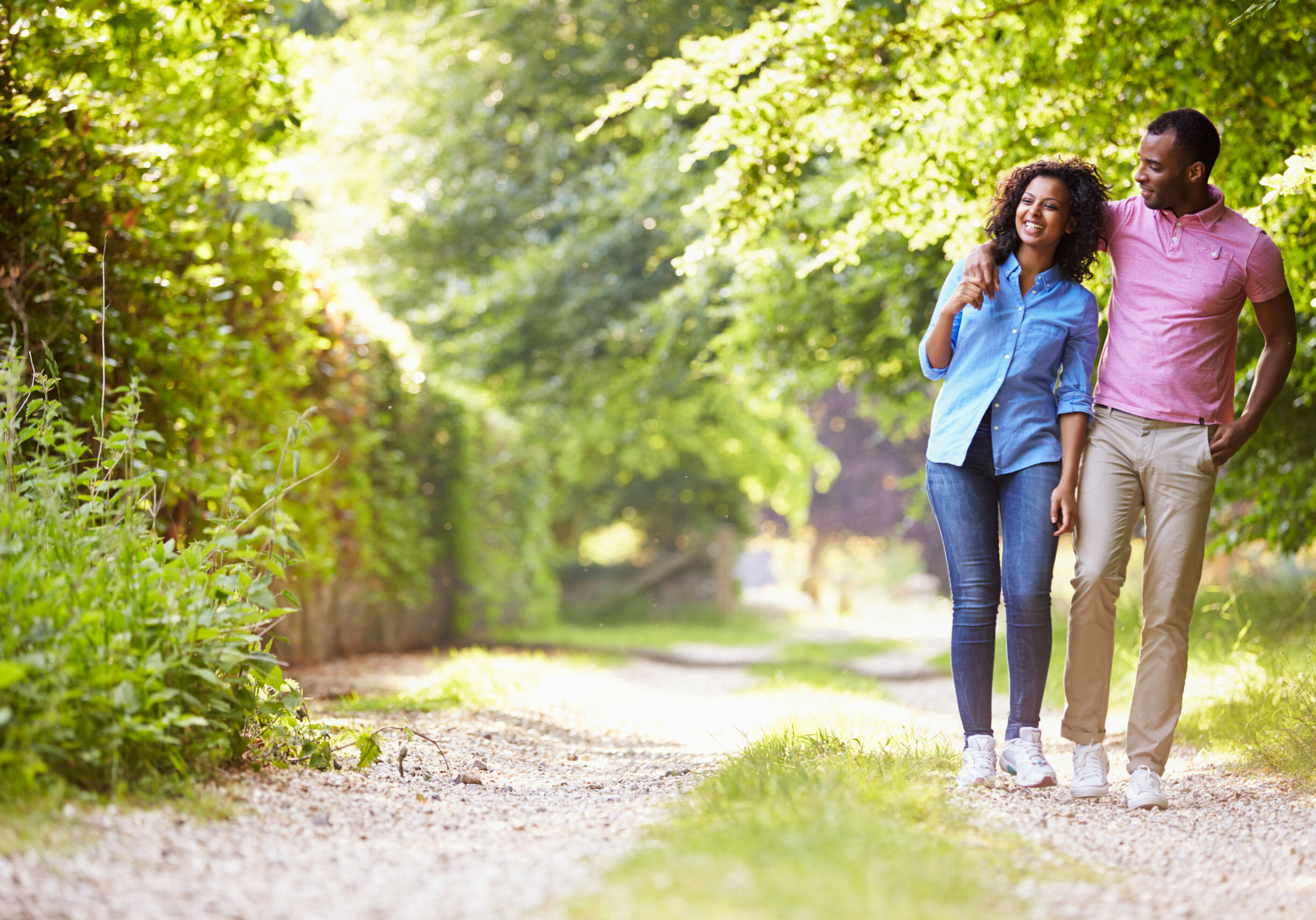 Young African American Couple Walking In Countryside On Sunny Day