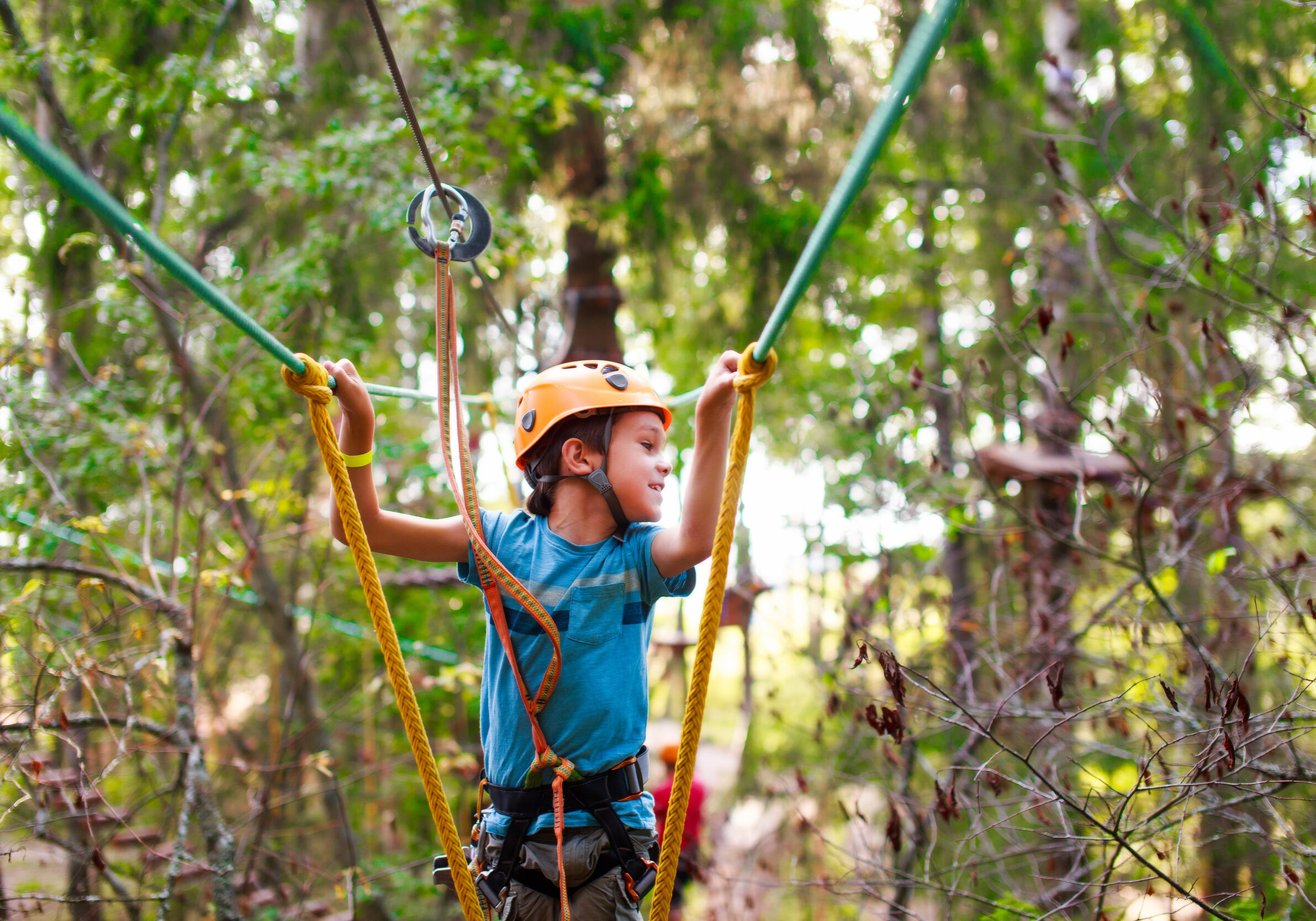 cheerful child bravely overcomes extreme rope route outdoors. ziplining