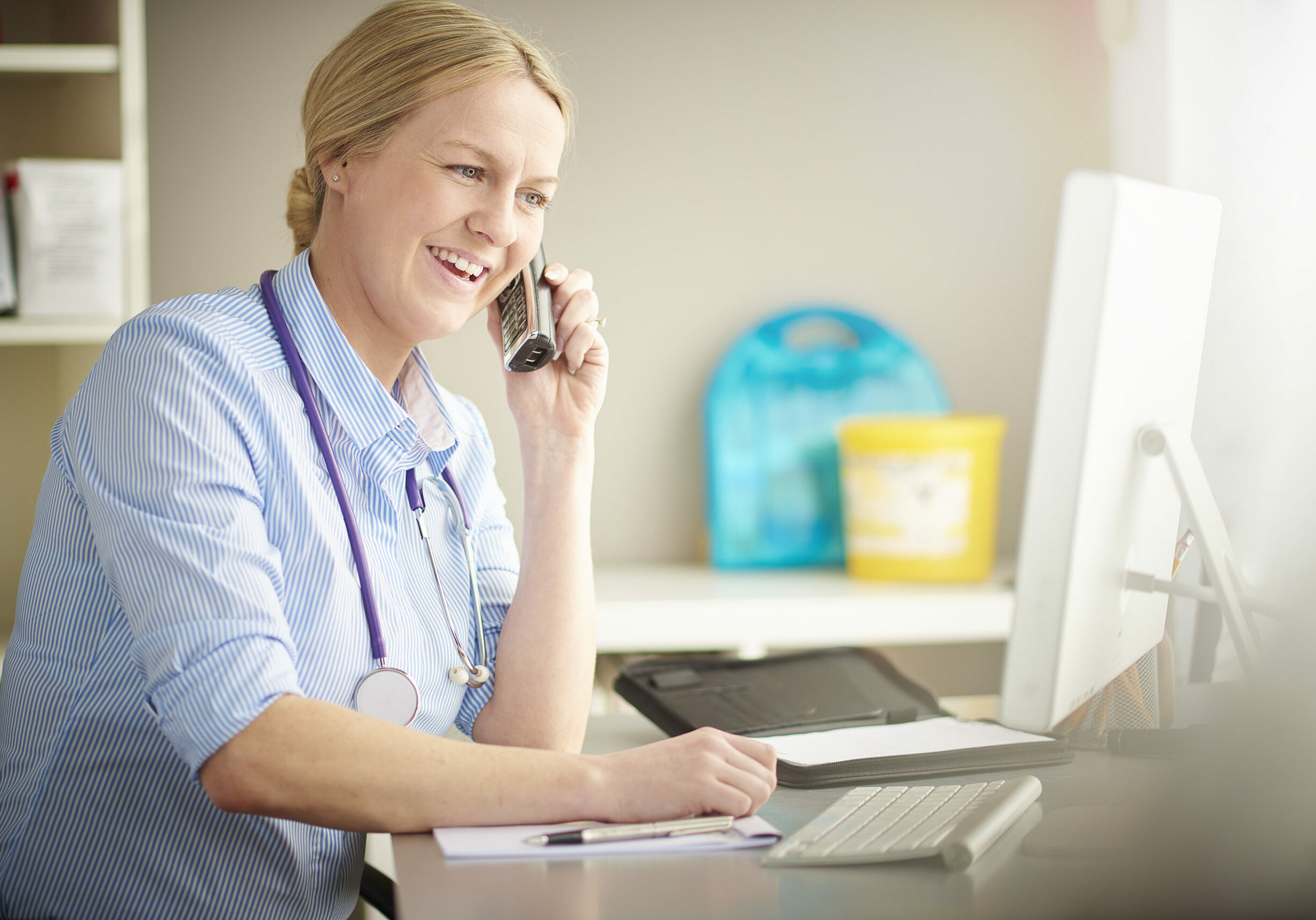 a female doctor on the phone to her patient with the test results