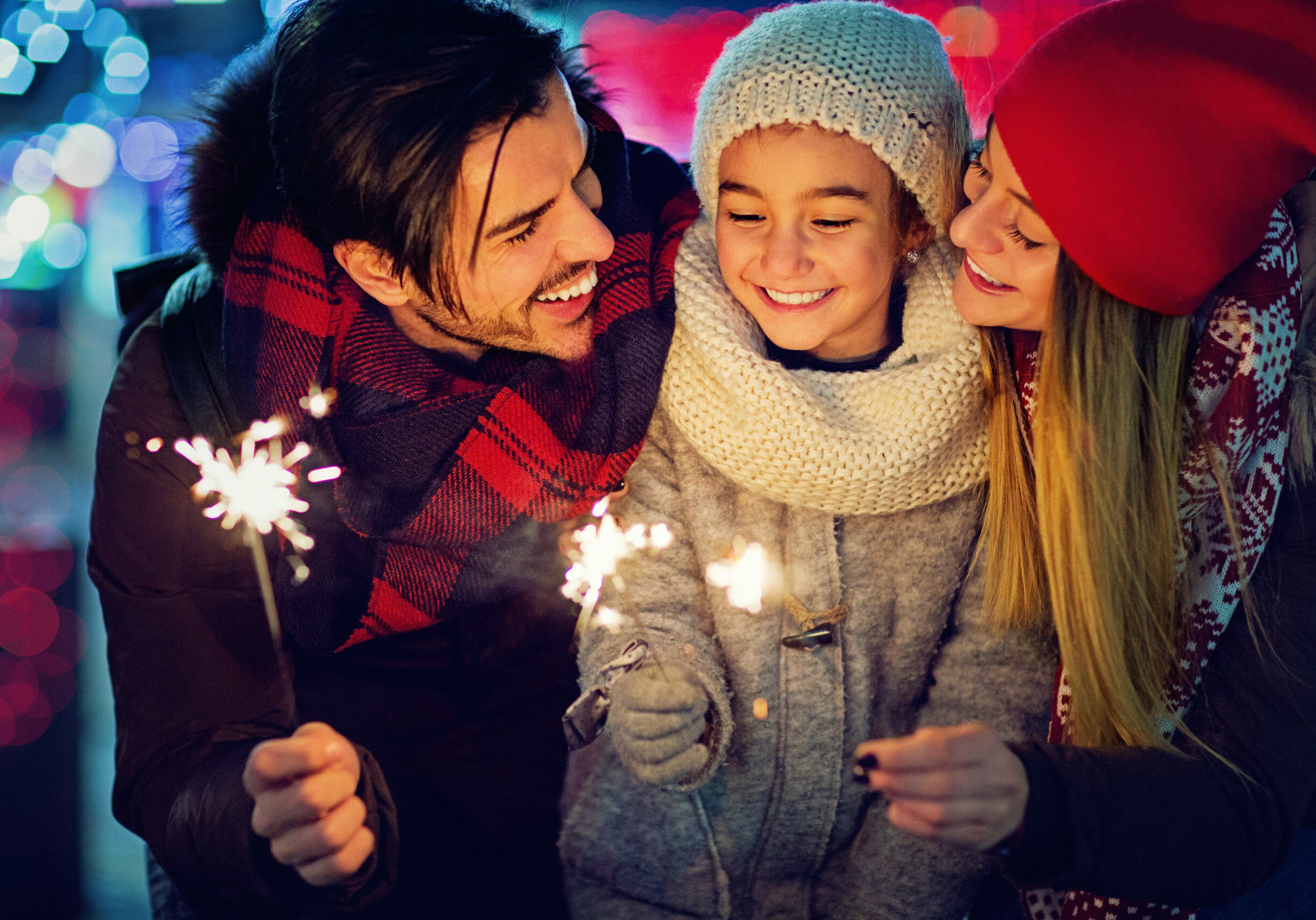 Young, happy couple is hugging their daughter and holding fireworks at Christmas