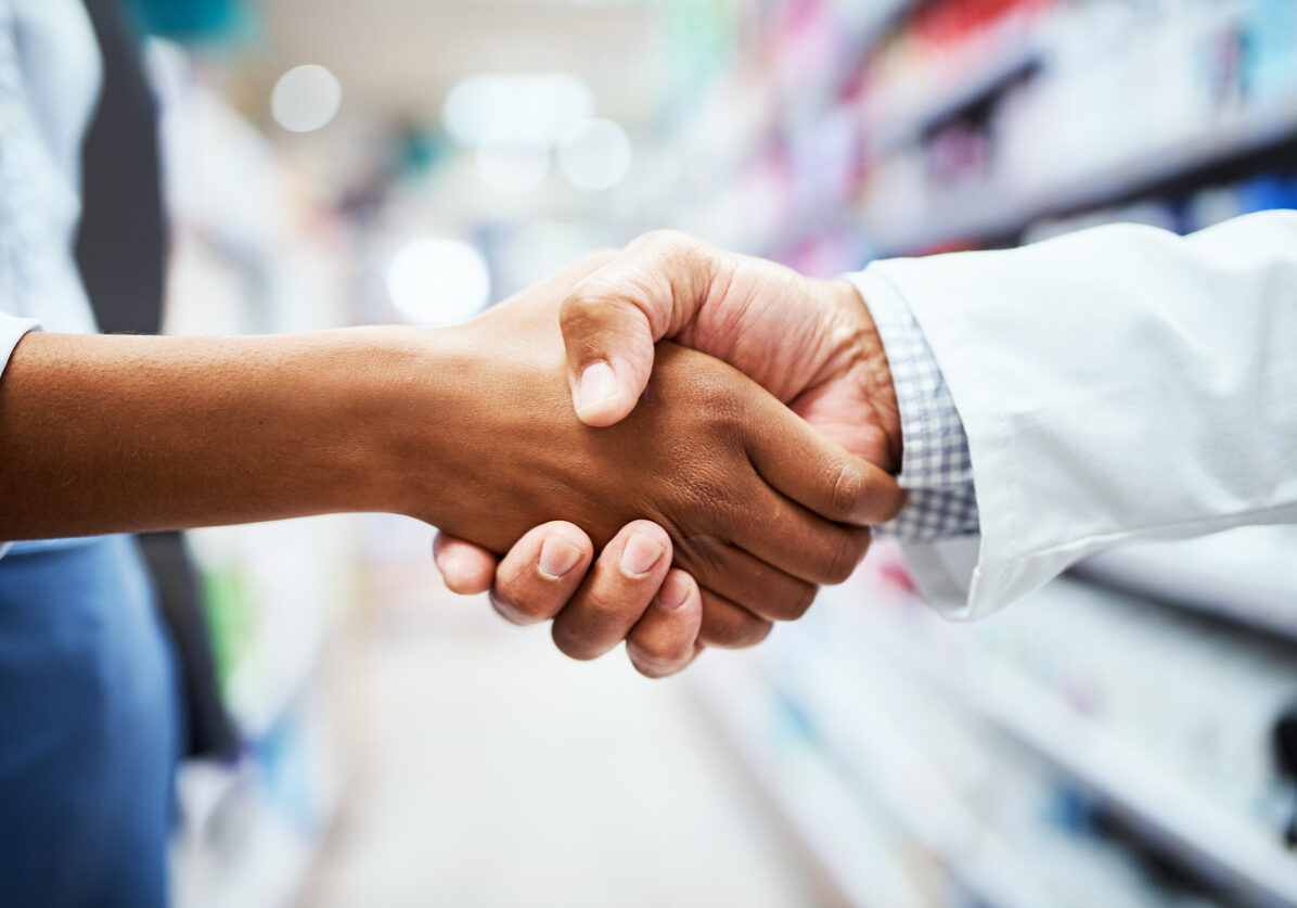 Closeup shot of an unrecognizable pharmacist shaking hands with a customer in a chemist